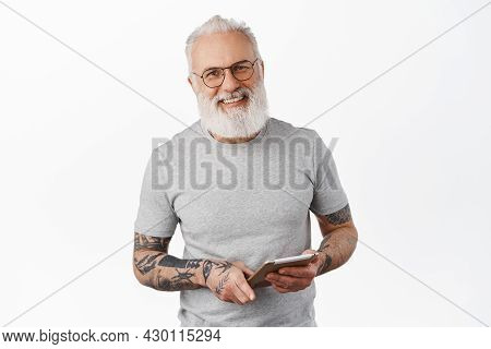 Handsome Senior Man In Glasses With Tattoos, Holding Digital Tablet And Smiling At You With Happy Ca
