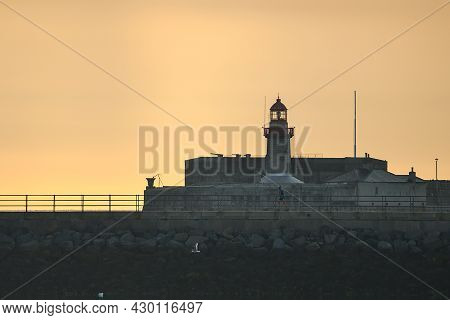 Beautiful Early Morning View Of Red East Pier Lighthouse Against Epic Hazy Orange Sunrise Sky With A
