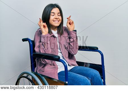 Young brunette woman sitting on wheelchair gesturing finger crossed smiling with hope and eyes closed. luck and superstitious concept.