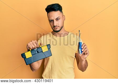 Young arab man holding toolbox and screwdriver skeptic and nervous, frowning upset because of problem. negative person.