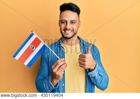 Young arab man holding costa rica flag smiling happy and positive, thumb up doing excellent and approval sign