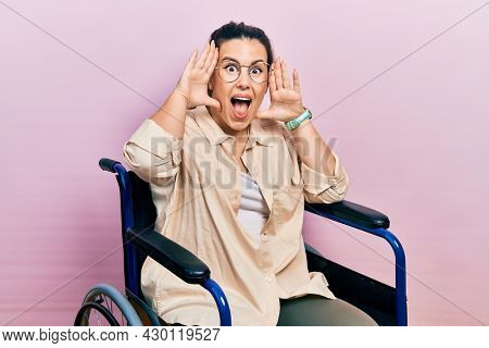 Young hispanic woman sitting on wheelchair smiling cheerful playing peek a boo with hands showing face. surprised and exited