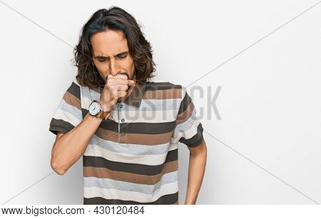 Young hispanic man wearing casual clothes feeling unwell and coughing as symptom for cold or bronchitis. health care concept.