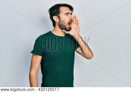 Young hispanic man wearing casual white tshirt shouting and screaming loud to side with hand on mouth. communication concept.