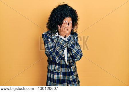 Young latin girl wearing business clothes with sad expression covering face with hands while crying. depression concept.