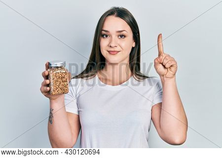 Young hispanic girl holding lentils bowl smiling with an idea or question pointing finger with happy face, number one