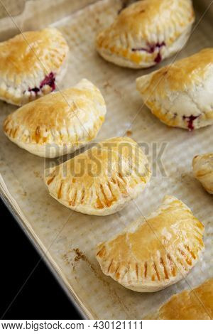 Homemade Cherry Hand Pies In A Baking Pan On A Black Surface, Side View. Close-up.