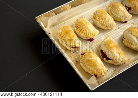 Homemade Cherry Hand Pies In A Baking Pan On A Black Surface, Side View. Copy Space.