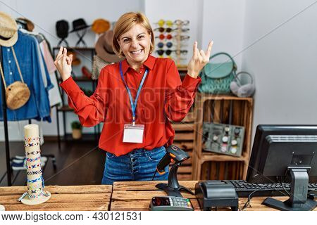 Middle age blonde woman working working as manager at retail boutique shouting with crazy expression doing rock symbol with hands up. music star. heavy concept.