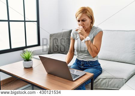 Middle age blonde woman using laptop at home feeling unwell and coughing as symptom for cold or bronchitis. health care concept.
