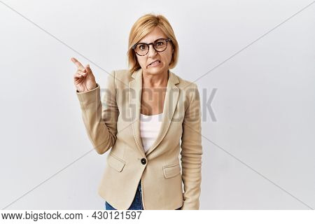 Middle age blonde business woman standing over isolated background pointing aside worried and nervous with forefinger, concerned and surprised expression