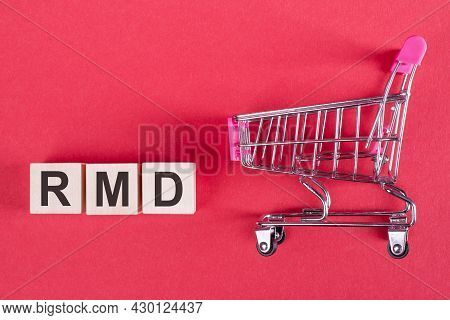 The Word Rmd - Required Minimum Distribution, On Wooden Cubes, On A Pink Background With A Shopping