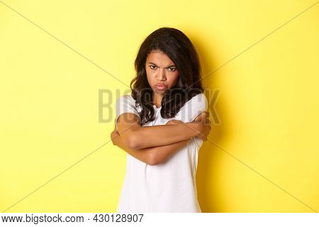 Image Of Moody Cute African-american Girl, Hugging Herself And Sulking With Offended Expression, Sta