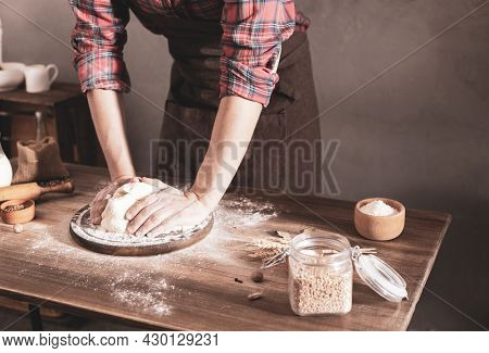 Baker man making dough and bakery ingredients for homemade bread cooking on table. Bakery concept and male hand