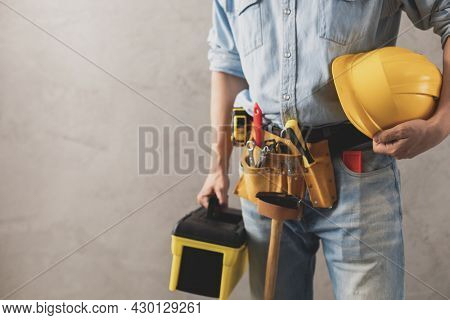 Worker man holding construction helmet and toolbox near wall. Male hand and tools for house room renovation. Home renovation concept