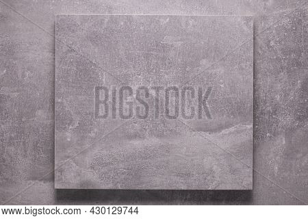 Abstract grey background texture at table or wall. Front view of gray panel plate as sign at wall background surface