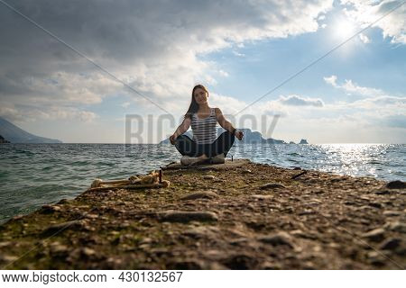 Young Active Brunette Is Sitting In Lotus Position On Rocky Seashore, Front View From Low Angle, Bea
