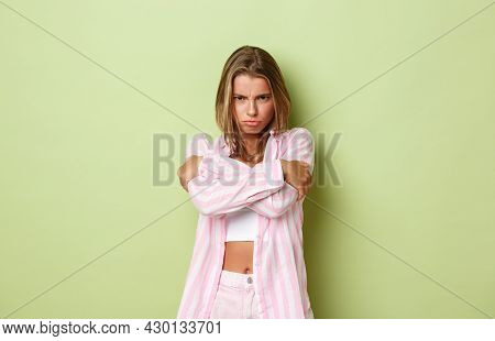 Image Of Timid Sulking Girl With Blond Hair, Sulking And Feeling Mad At Someone, Embracing Herself A