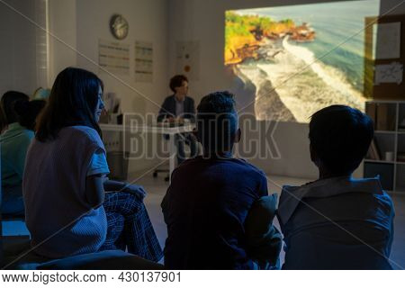 Group of schoolkids watching video about natural environment in dark classroom