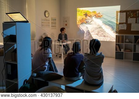 Schoolkids watching movie about natural environment at lesson of biology
