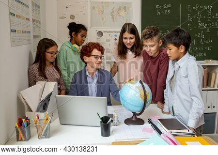 Group of multiracial schoolkids standing by desk of their teacher and looking at earth model