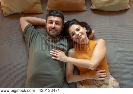 Cheerful and affectionate young couple lying on bed in front of camera