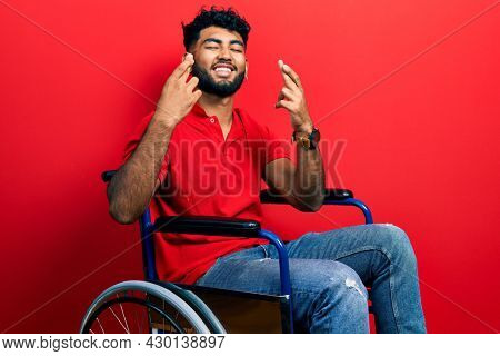 Arab man with beard sitting on wheelchair gesturing finger crossed smiling with hope and eyes closed. luck and superstitious concept.