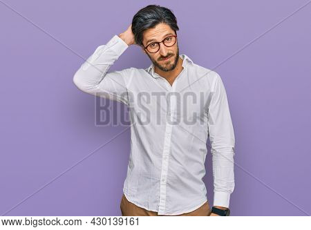Young hispanic man wearing business shirt and glasses confuse and wonder about question. uncertain with doubt, thinking with hand on head. pensive concept.