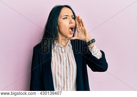 Young hispanic girl wearing business clothes shouting and screaming loud to side with hand on mouth. communication concept.