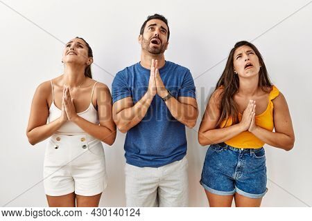 Group of young hispanic people standing over isolated background begging and praying with hands together with hope expression on face very emotional and worried. begging.