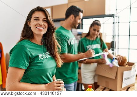 Group of hispanic volunteers smiling happy working at charity center.