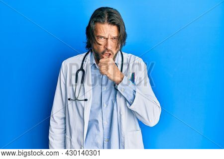 Middle age handsome man wearing doctor uniform and stethoscope feeling unwell and coughing as symptom for cold or bronchitis. health care concept.