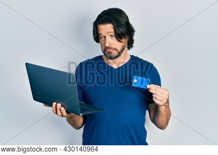 Middle age caucasian man wearing business style holding laptop and credit card depressed and worry for distress, crying angry and afraid. sad expression.