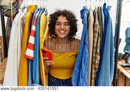 Young hispanic woman searching clothes on clothing rack using smartphone winking looking at the camera with sexy expression, cheerful and happy face.