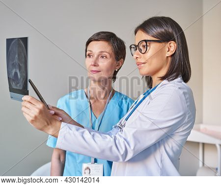 Two Women Doctors In Uniform Looking At Brain Tomography And Discussing Diagnosis, Young African Fem