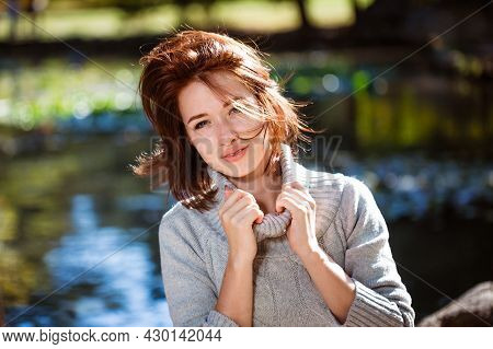 Portrait Of Young Woman Of Caucasian Appearance Posing In Sweater In An Autumn Park On A Sunny Day.