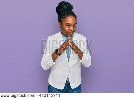 Young african american woman wearing business clothes hands together and fingers crossed smiling relaxed and cheerful. success and optimistic