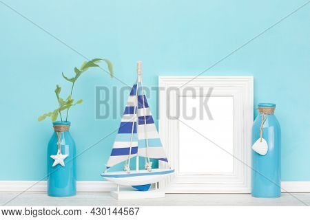 Background mockup template with shabby chic, rustic vertical picture frame, wooden sail boat, decorated vases, one with fern leaves in front of blue wall, inner frame isolated with clipping path