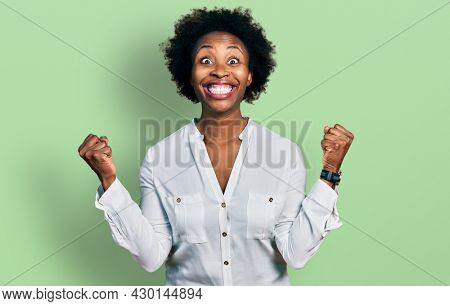 African american woman with afro hair wearing casual white t shirt celebrating surprised and amazed for success with arms raised and open eyes. winner concept.