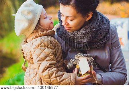 Mother And Her Little Daughter Hold Glass Jar Filled With Yellow And Green Leaves, Berries And Seeds