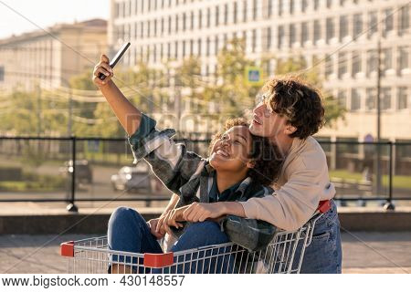 Two happy and affectionate millennials making selfie in urban environment