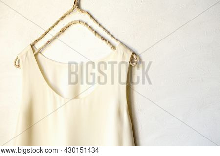 Beige Or White Tank Top Hanging On A Hanger In A White Wall. Close Up And Copy Space.