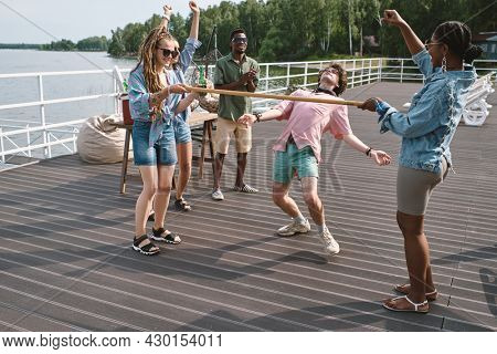 Friends cheering for young man bending backwards to walk under vertical bar playing limbo