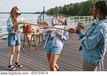 Joyful pretty young woman in sunglasses enjoying playing limbo game with her friends at birthday party
