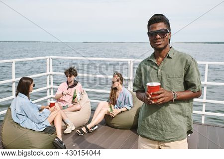 Young Black man attending party on wooden pier by lake, he is drinking booze and looking at camera