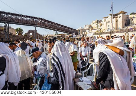 JERUSALEM, ISRAEL - SEPTEMBER 26, 2018: Touching ceremony at the Western Wall. Jews praying wrapped in festive white Talit. The blessing of the Cohanim. The concept of pilgrimage