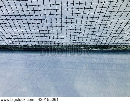 Black Nylon Tennis Net And Light Blue Court In A Half-half Frame, Used For Background