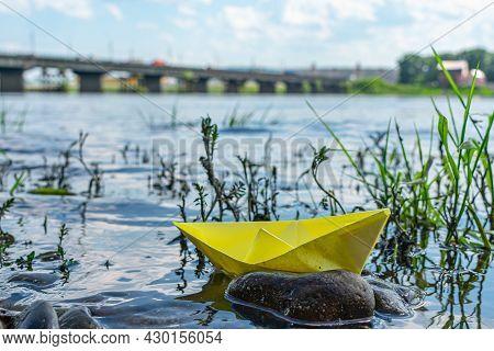 A Paper Boat Shipwreck Near A Rocky River Bank. Conceptual Photo Showing Potential Hazards In Mariti