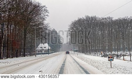 Driving in a snowstorm on a countryroad in the Netherlands in winter