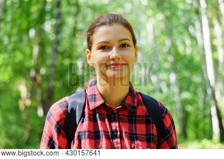 Portrait Of A Young Girl In A Red Shirt On A Green Unfocused Forest Background. Selective Focus